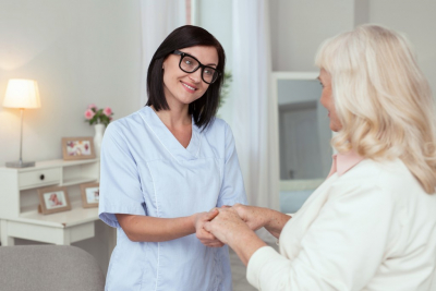 caregiver holding the hands of her senior patient