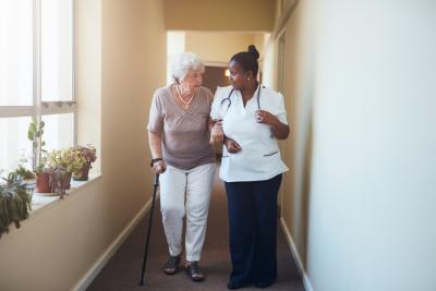senior woman walking with her nurse